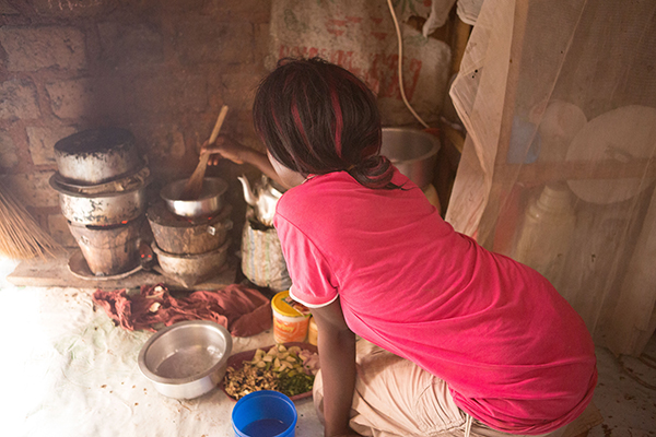 Cooking inside on a charcoal stove. Slums, Uganda