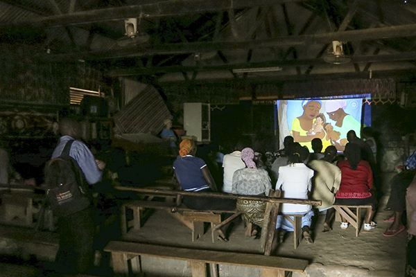 Showing an educational video on pneumonia at a local cinema. Kampala slums.
